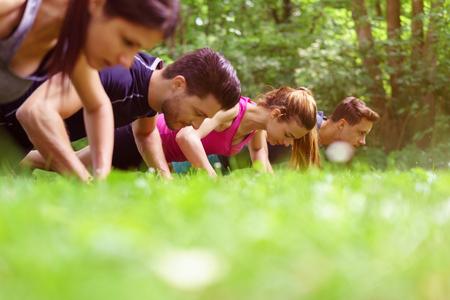 自分の頭と肩の草の上を渡って極端な低角度表示が付いている公園の屋外で腕立て伏せをやって作業 2 つの若いカップル