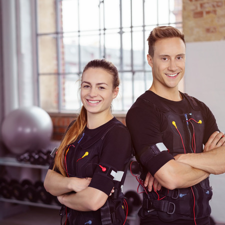 Male and female fitness instructors stand together while wearing biometric trackers in exercise studio near tall windows