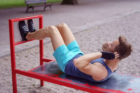 man sit: Fit young man working out outdoors doing sit ups on a red metal bench in a park Stock Photo