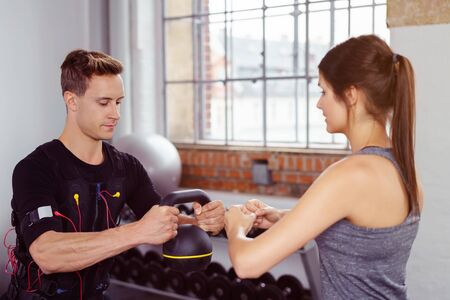 neuromuscular: Female instructor works with male athlete as he holds kettle bell and squats while exercising in fitness studio