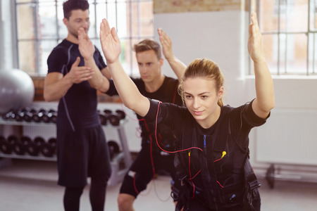 neuromuscular: Male instructor assisting students in special wearable technology jackets as they perform stability squatting exercises in gym with weight racks near window in background Stock Photo