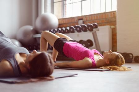 骨盤底筋エクササイズ重みとジムでバック グラウンドで安定性のボールを個々 の長方形のマットの上 2 つの若い大人の女性
