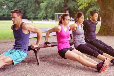 Группа из четырех взрослых мужчин и женщин, выполняющих погружения на скамейке в парке летом на открытом воздухе Фото со стока
