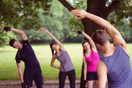 aerobic instructor: Group of diverse young friends doing outdoor aerobic exercises in a park following the lead of a male instructor
