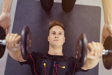 hand held: Serious man exercising with hand held weights while lying down on a yoga mat and being helped by instructor Stock Photo