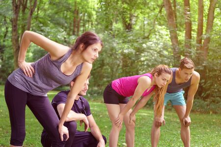 weary: Four weary friends resting after working out in a park leaning forwards on their knees in their sportswear in a healthy lifestyle concept Stock Photo