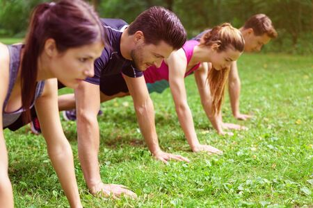 couples outdoors: Two couples doing crossfit exercises performing push-ups in the planking position on green grass outdoors in a park