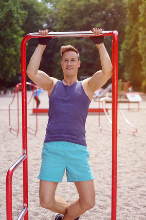 outdoor fitness: Single smiling handsome athletic man in purple shirt, blue pants and black gloves doing chin ups outdoors Stock Photo