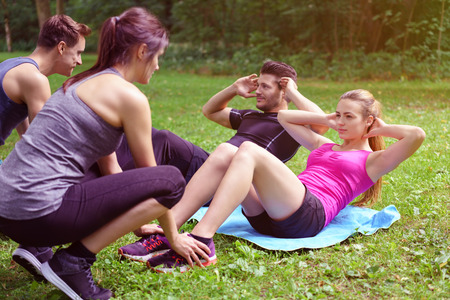Two young couples working out in a park with one couple doing sit ups assisted by the second man and woman holding their feet