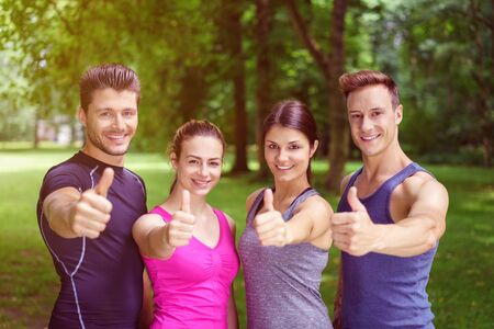 fitness motivation: Two happy motivated fit young couples giving a thumbs up of approval and success and they pose in their sportswear in a park smiling at the camera