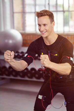 neuromuscular: Energetic man exercising in fitness studio dressed entirely in black besides hand held weights Stock Photo