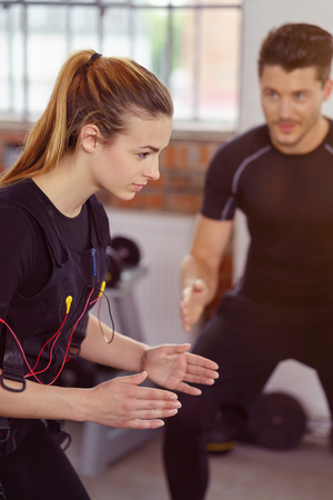 neuromuscular: Woman wearing biometric fitness tracker with wires as she exercises and is supervised by her instructor