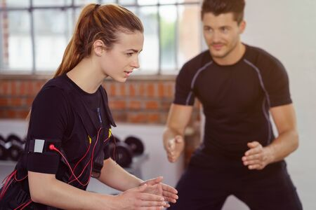neuromuscular: Male fitness instructor works with woman wearing biometric equipment as she exercises in a studio