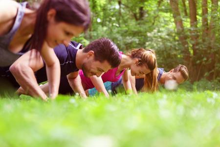 Čtyři mladí lidé dělá kliky v parku během fitness cvičení vnímány velmi nízký úhel po trávě