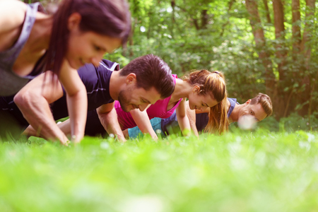 Four young people doing push-ups in a park during a fitness workout viewed very low angle across the grass