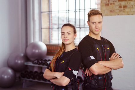 Female and male confident athletes with folded arms dressed in wearable technology in gym with weight racks and stability balls in background