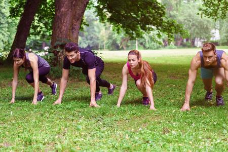 Cuatro jóvenes agazapados en la posición de arranque listo para correr a través de un parque durante su rutina de entrenamiento diario en un concepto de estilo de vida activo y saludable