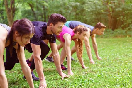 agachado: Cuatro jóvenes, dos hombres y dos mujeres, se agacharon en la posición de arranque en un parque verde listo para hacer el entrenamiento de velocidad
