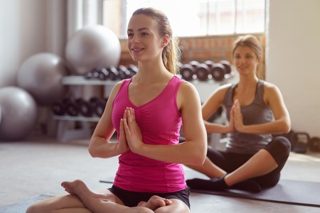 Two pretty happy young woman meditating in a gym on their yoga mats in the lotus position during a workout with gym equipment visible behind Stock Photo