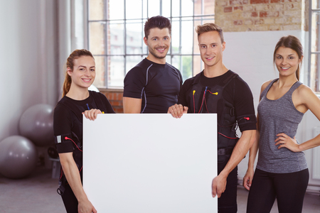 Fitness team in a gym with four smiling young people, two men and two women, holding a blank sign with copy space in front of them Stock Photo