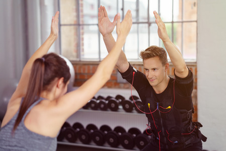 neuromuscular: Handsome grinning young man in dark, heavily wired fitness tracking or sensory vest exercising with woman in gym near dumbbell weights Stock Photo