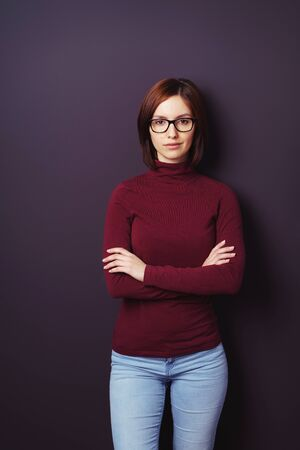 thirties: Confident young woman wearing glasses and jeans standing facing the camera with folded arms and a serious expression on a dark background