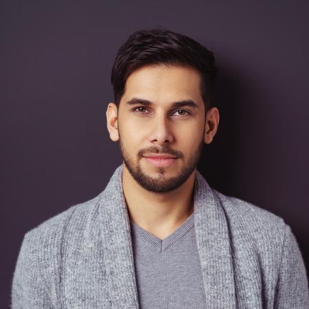 Nachdenklich hübscher bärtiger junger Mann starrte nachdenklich an die Kamera in einem stilvollen grauen Pullover und Top, Nahaufnahme Kopf und Schultern quadratischen Format