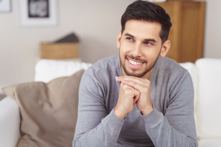 leaning forward: Handsome bearded man in gray shirt leaning forward while sitting on sofa with hands under his bearded chin Stock Photo