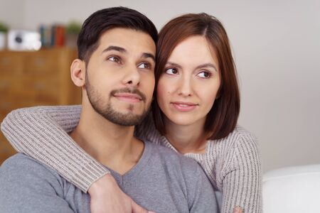 to ponder: Attractive young couple sitting together in an embrace on sofa in living room while looking upward as if to dream about or ponder something