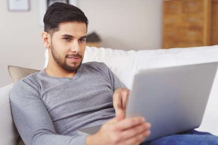 homey: Handsome bearded young man in gray shirt and blue jeans with pleased expression sitting on sofa reading something on a tablet computer in his hands Stock Photo