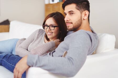 laying on back: Handsome bearded young man in gray long sleeve shirt laying back on sofa with girlfriend looking at something out of the frame