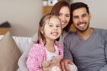 vivacious: Cute vivacious little girl laughing at the camera as she poses with her parents on a sofa in a happy family portrait