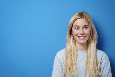 confident woman: Cute blond woman wearing plain grey sweater smiles at camera as she stands against bright blue wall