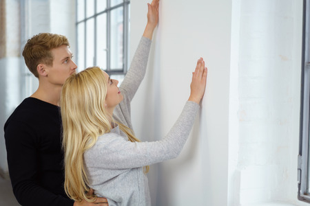 facing a wall: Young couple planning the layout of a new home standing facing a wall measuring with their hands the placement of an item of furnishing