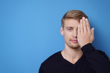 one eye: Single cute handsome young bearded man covering one eye with hand over blue background with copy space