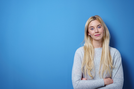 jaunty: Cute pert young blond woman with a jaunty expression standing with folded arms looking at the camera on a blue background with copy space