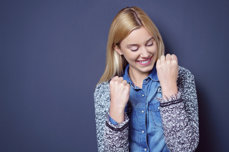 Single relieved and happy young woman in blond hair, sweater and blue shirt with clenched fists while looking downward in celebration over dark background with copy space