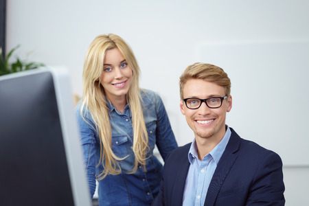 alongside: Smiling confident businessman wearing glasses sitting at his desk with a female co-worker standing alongside beaming at the camera