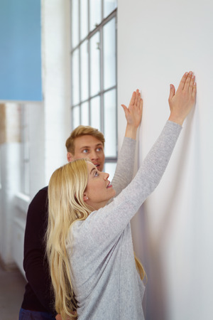 visualise: Young couple planning their new apartment interior with the young woman standing extending her hands up on a wall as they visualise a fixture