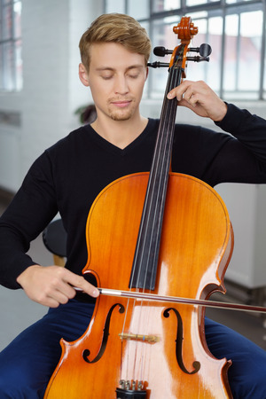 cellos: Calm young male viola or cello player in blue jeans and black long sleeve shirt with closed eyes sitting with his instrument alone indoors Stock Photo