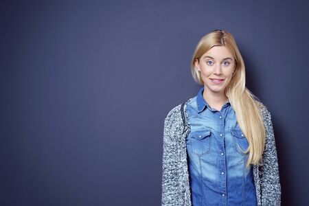 blue wall: Cute smiling single blond and blue eyed young woman in sweater looking friendly over dark background with copy space