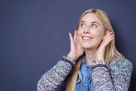 hands over ears: Happy cute young blond lady in sweater and blue buttoned shirt holding both hands to ears while looking upwards as if to listen to something over dark background with copy space