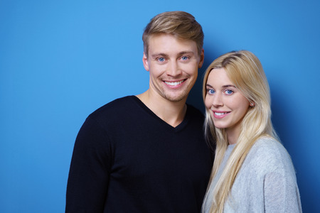 male hair: Attractive happy loving young couple posing arm in arm looking at the camera with warm friendly smile, on a blue background with copy space