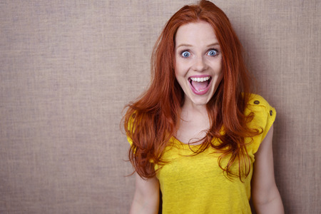 Pretty young redhead woman with a happy surprised expression of wide eyed delight standing against a beige background with copy space