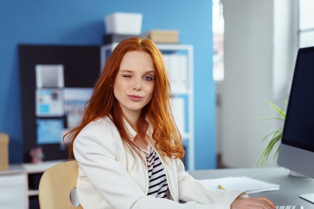 Beautiful serious young woman in long red hair and white blazer jacket with something in her eye or winking while typing on computer in small office with shelf and blue wall in background
