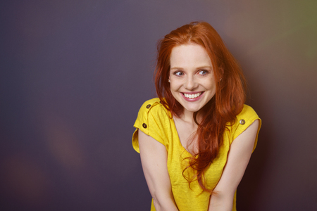 wonder: Single gorgeous young red haired woman in yellow shirt looking over while blushing or watching something over simple dark background with light flare and copy space