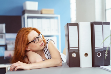 slumped: Overwhelmed red haired Caucasian woman in glasses and striped shirt slumped over at desk while looking at large work binders