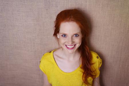 Single schitterende jonge roodharige vrouw in gele overhemd met vrolijke expressie over eenvoudige bruine doek achtergrond Stockfoto