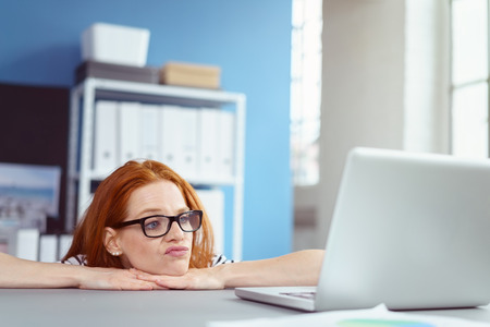 overwhelming: Frowning red haired female worker in eyeglasses with bored expression with hands under chin at desk behind laptop computer