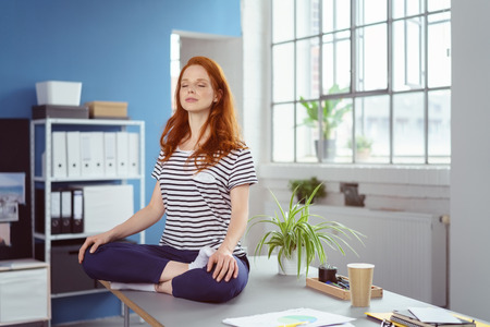Young woman meditating on her desk at the office sitting on her table in the lotus position with her eyes closed and a serene expression
